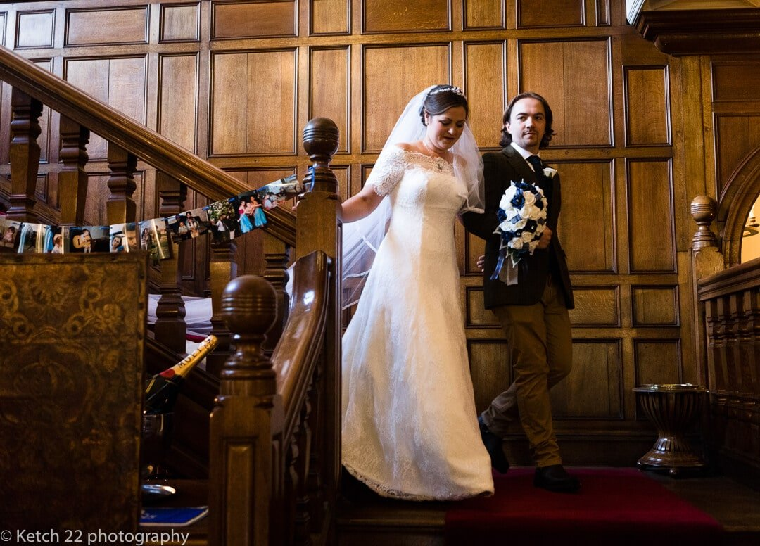 Bride coming down the stairs with brother at Country house wedding