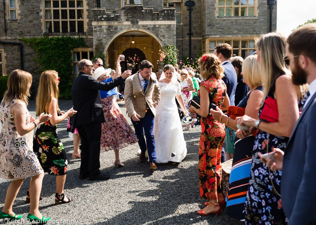 Wedding guests shower bride and groom with confetti at Herefordshire wedding