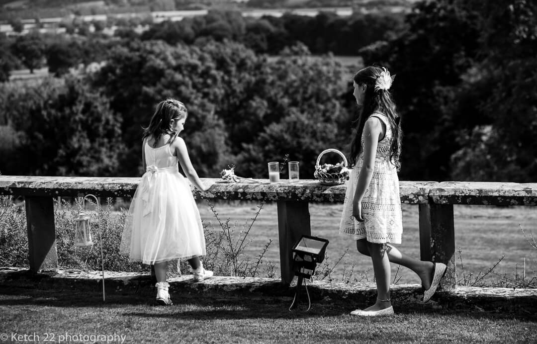 Flower girls leaning on wall in garden at summer wedding