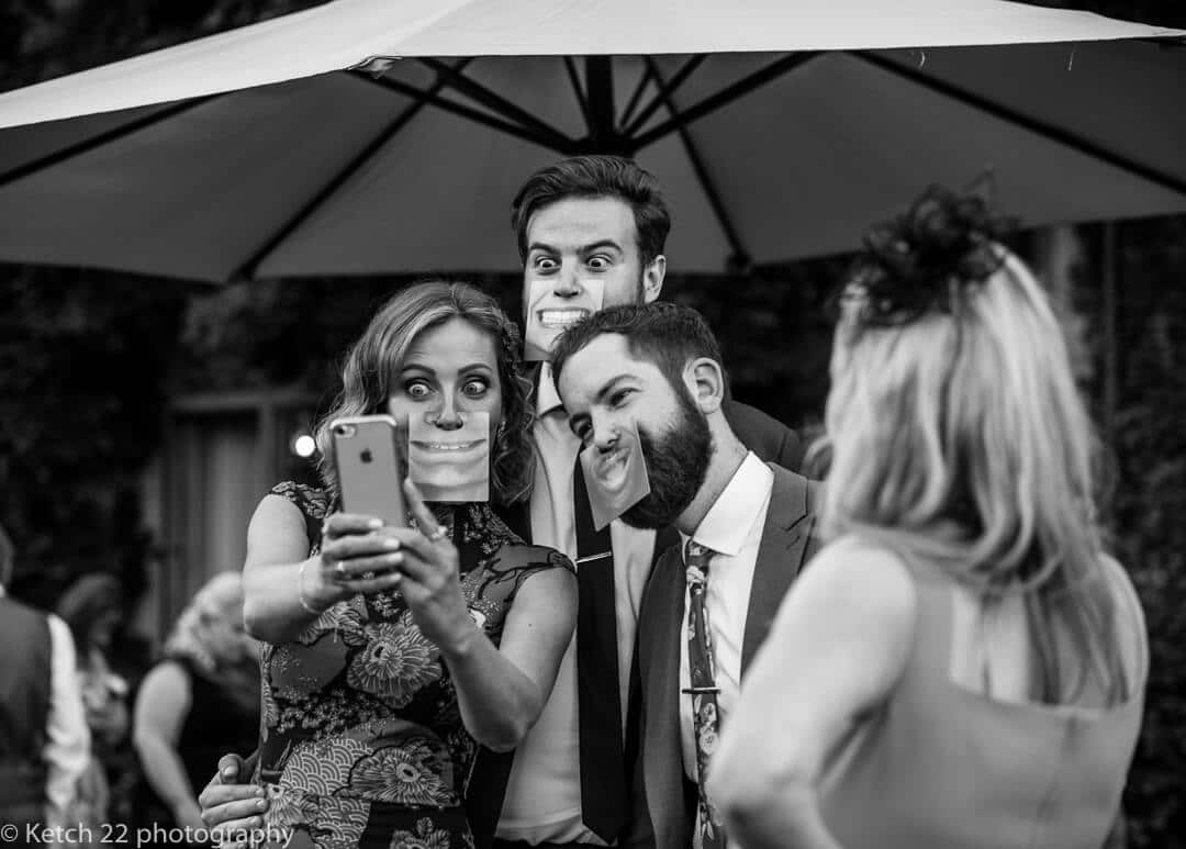 Wedding guests taking selfies with silly masks