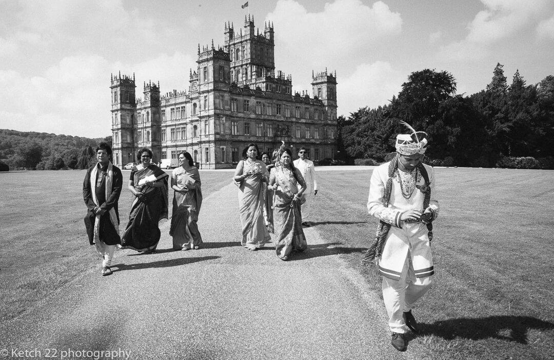 Groom walking in front of Highclere Castle at Hindu wedding