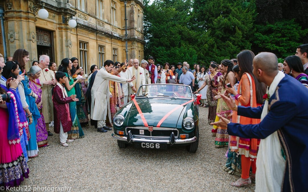 Bride and groom leaving wedding in green sports car