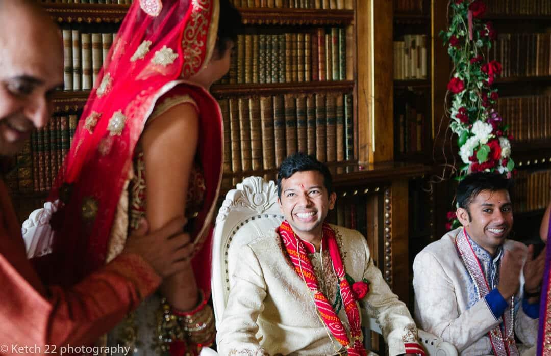 Groom wearing red flowers looking at bride