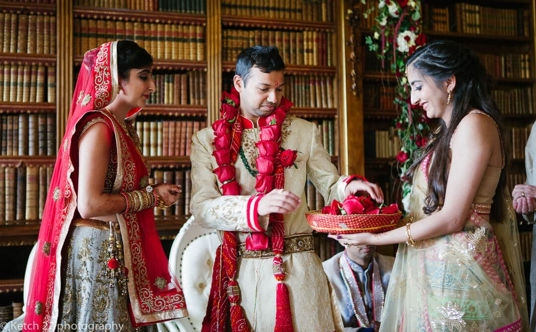 Groom receives red flowers at Highclere Castle