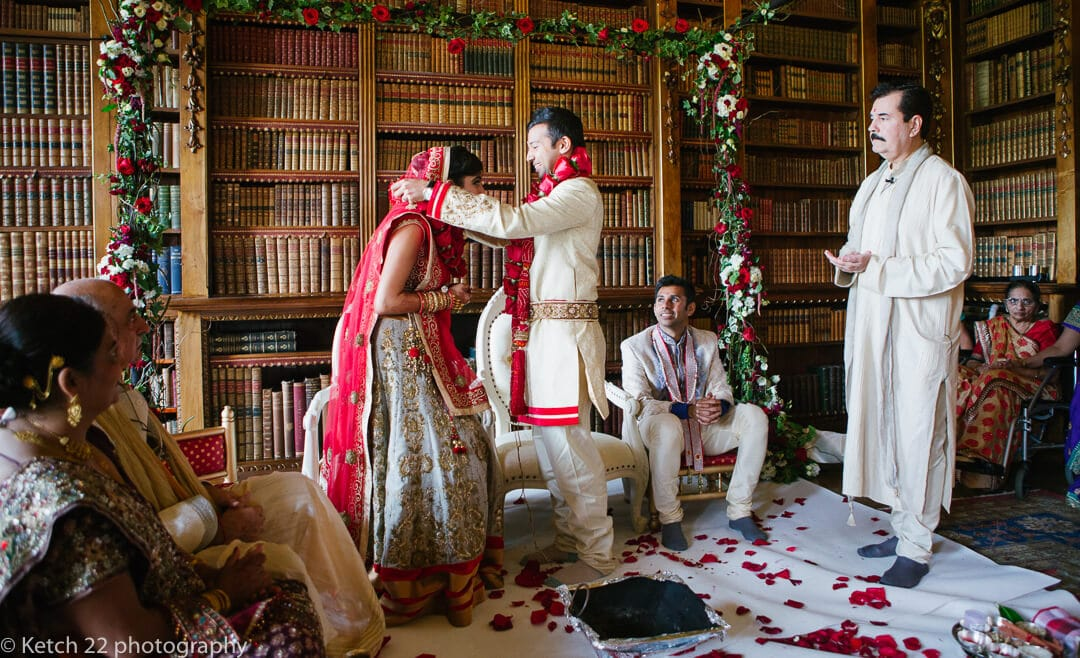Groom puts flowers around neck of hindu bride at Highclere Castle wedding