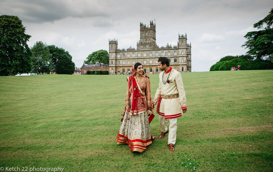 Bride and groom walking on lawn at Highclere Castle