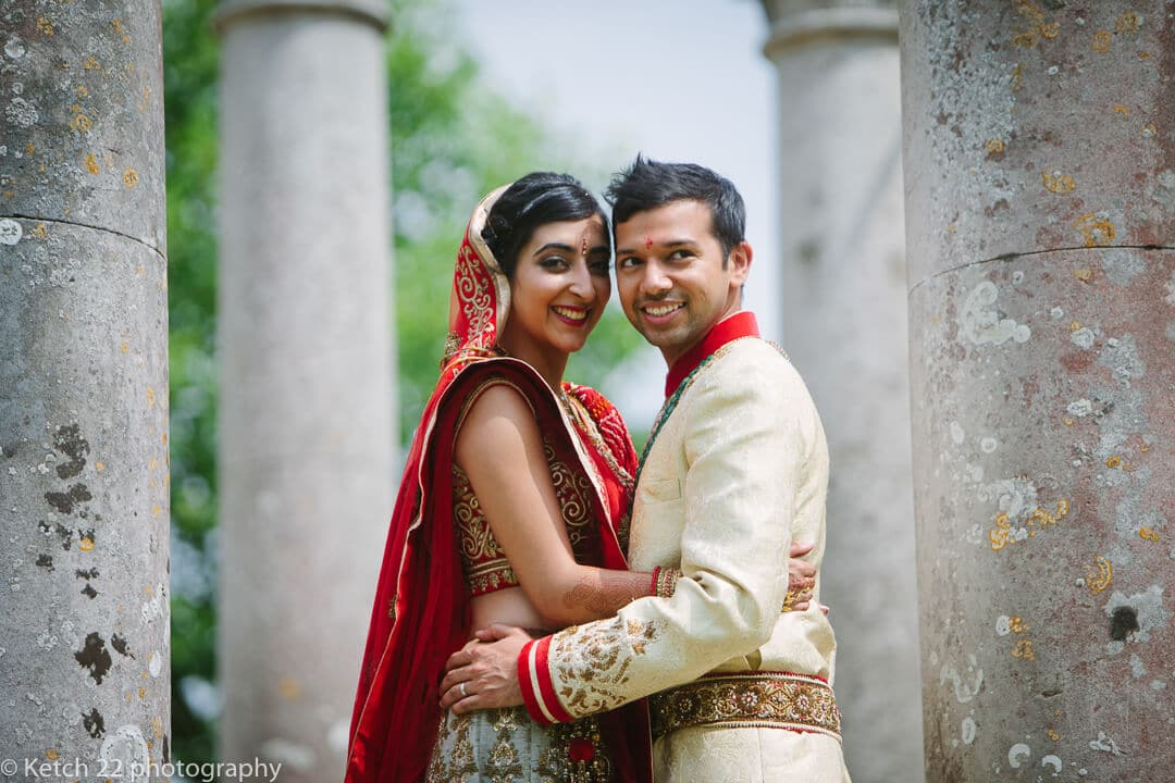 Hindu bride and groom by pillars at Highclere castle