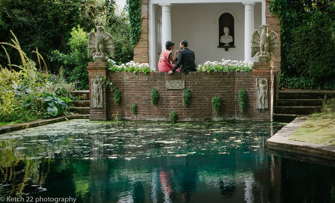 Indian bride and groom sitting in water garden at London wedding venue