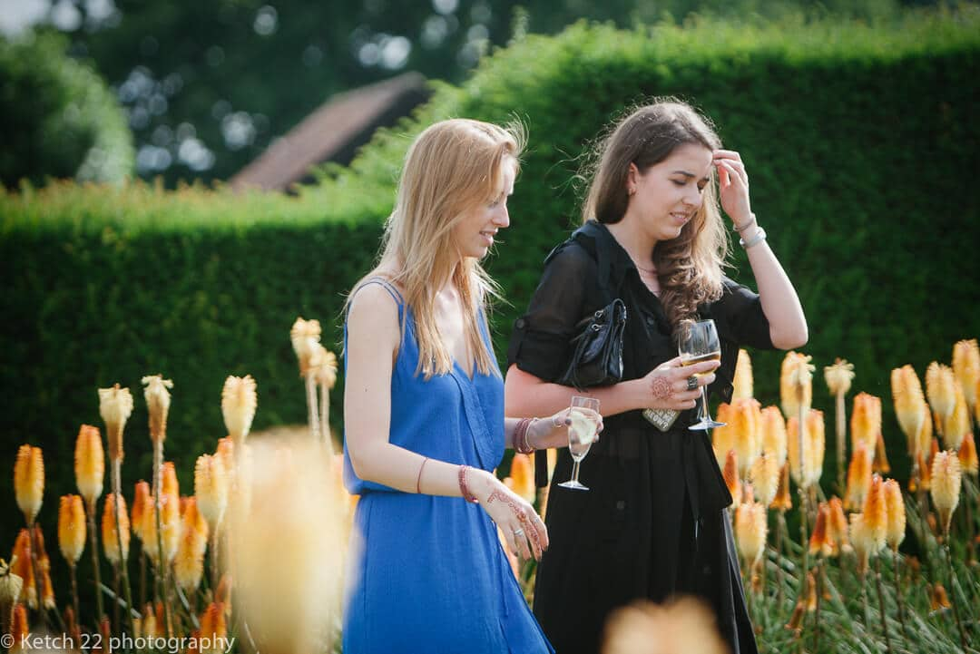 Wedding guests walking through garden with yellow flowers