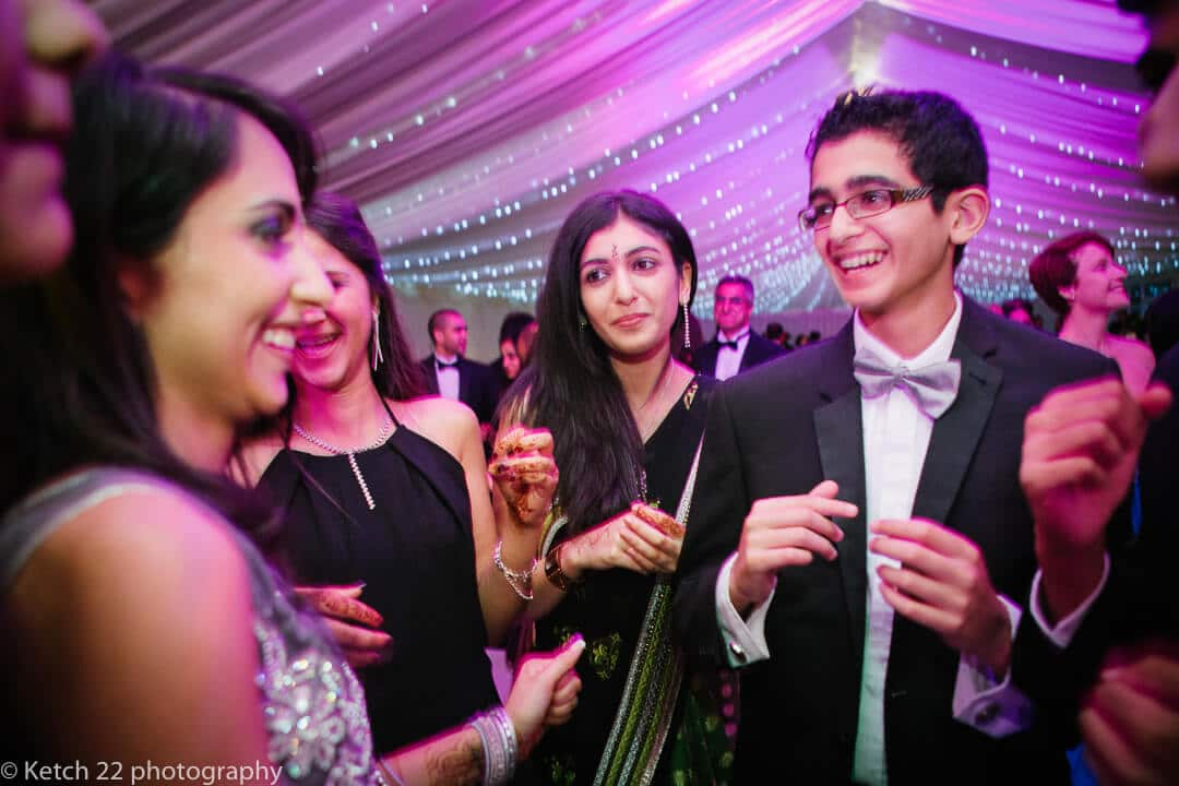 Wedding guests dancing at reception in marquee