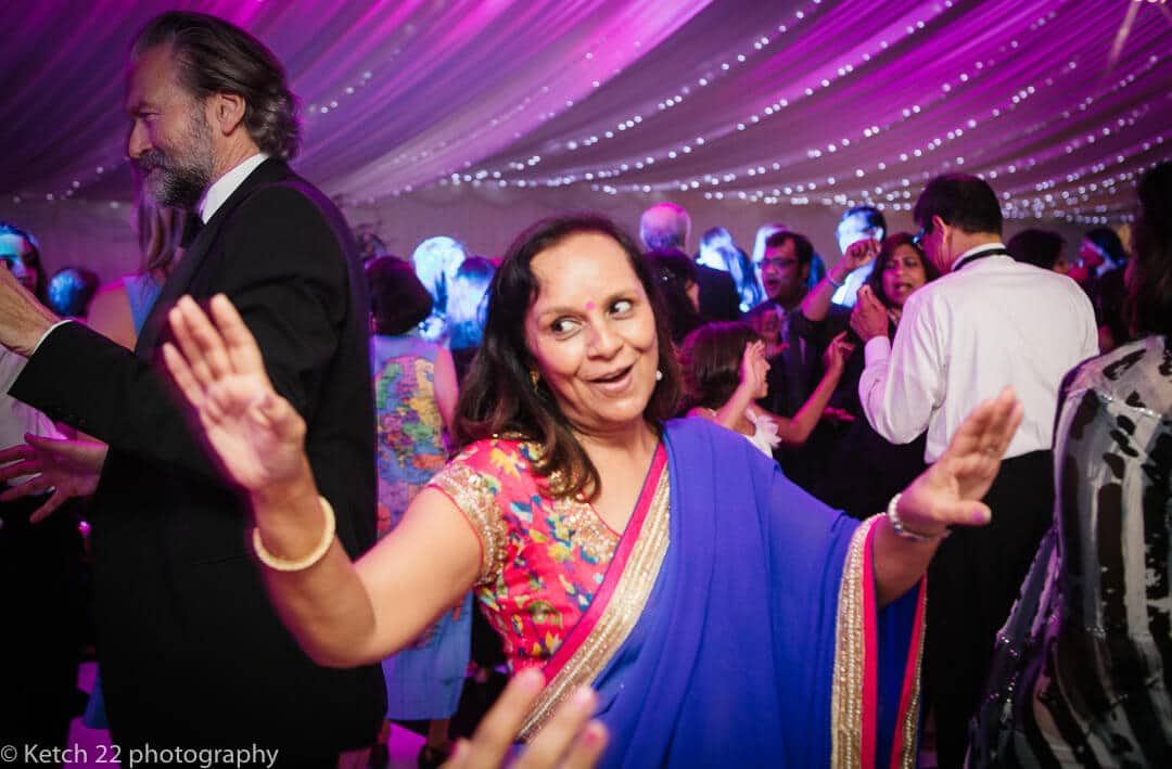 Hindu wedding guest in colourful sari dancing