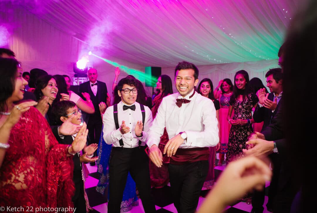 Groom dancing at Indian wedding reception at Micklefield Hall in London
