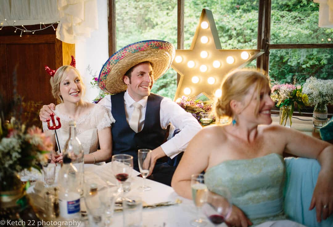 Bride and groom wearing mexican hat listen to wedding speeches