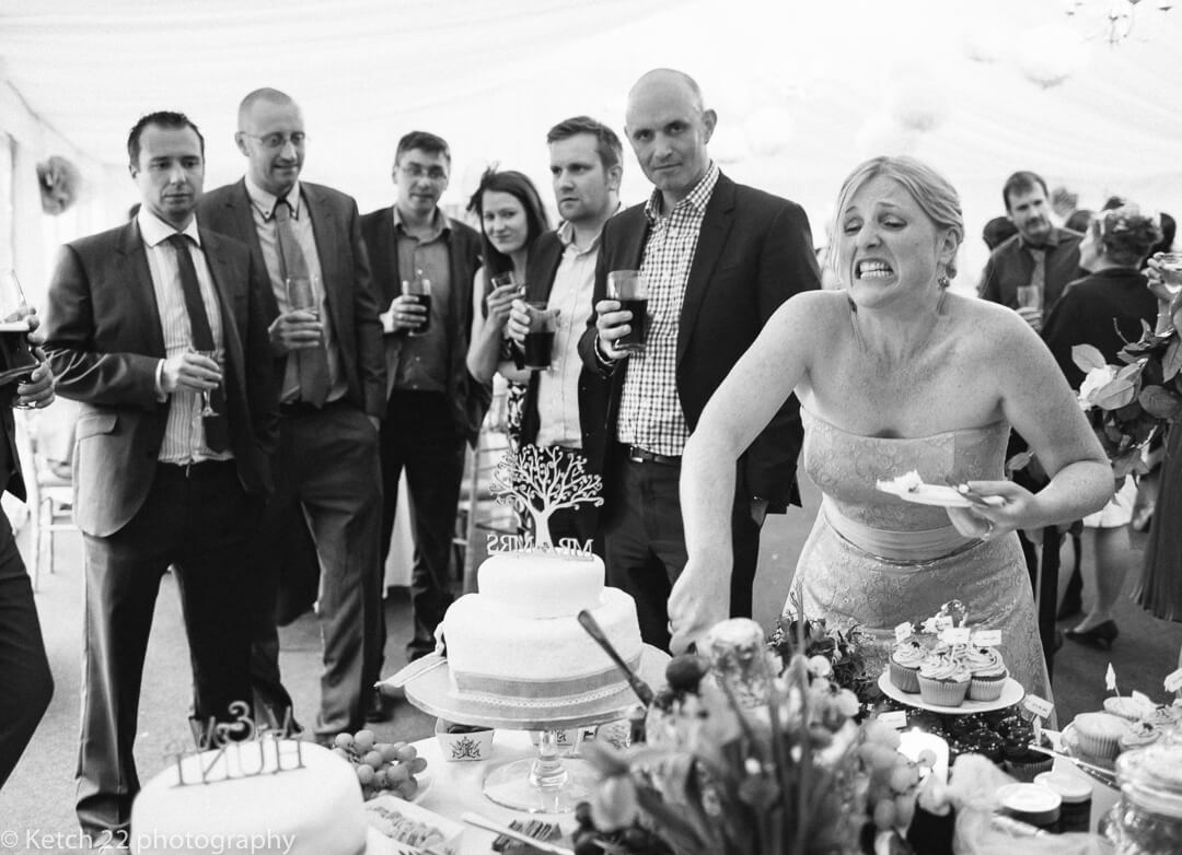 Funny photo of bridesmiad cutting the wedding cake