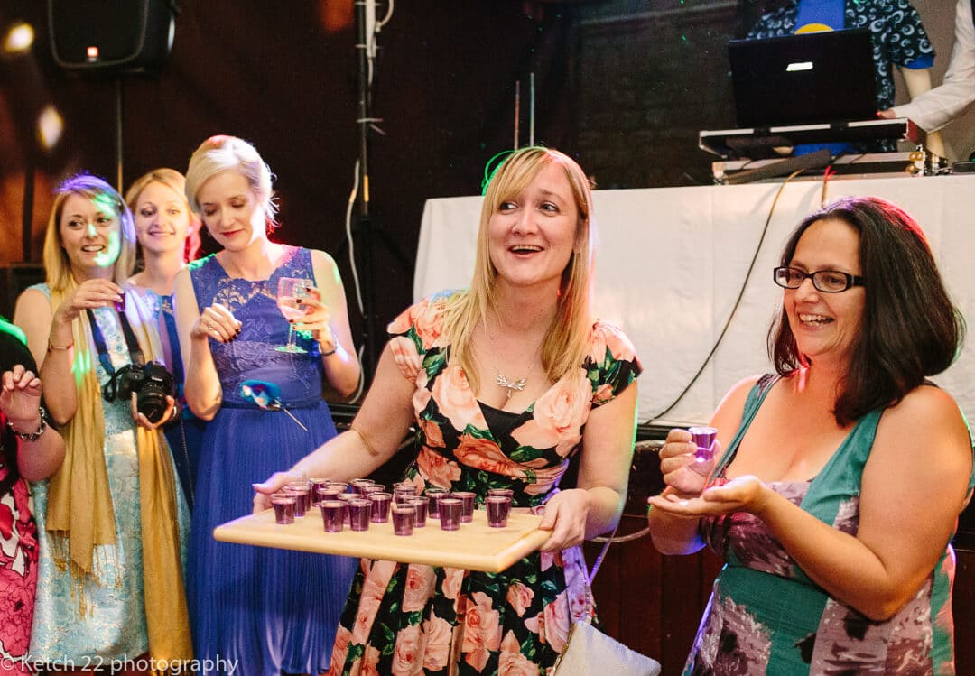 Wedding guest handing out purple shots at reception
