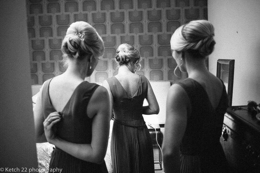 Black and white photo of three bridesmaids getting ready