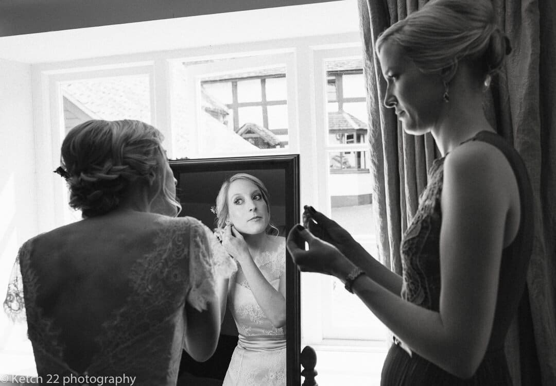 Bride looking in mirror at wedding preparations at The Green man in Herefordshire