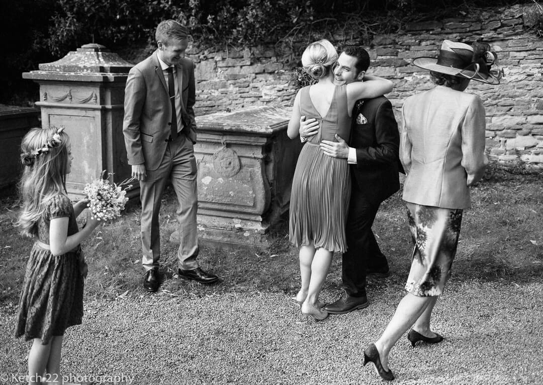 Groom greeting bridesmaid at How Caple Wedding