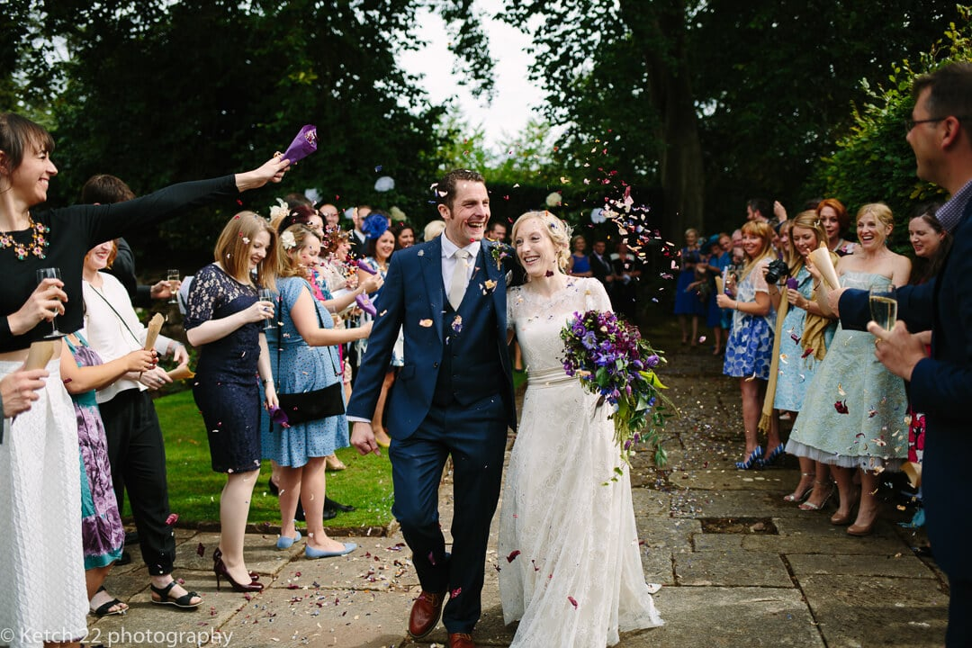 Excited bride and groom walking through confetti at How Caple Court In Herefordshire