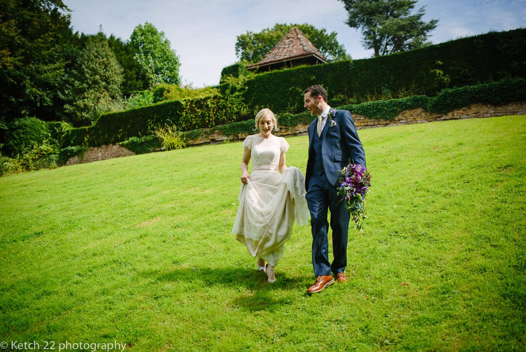 Bride and groom walking across green grass at rural wedding