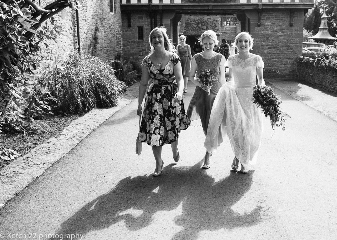 Bride and friends walking towards wedding reception at Country House