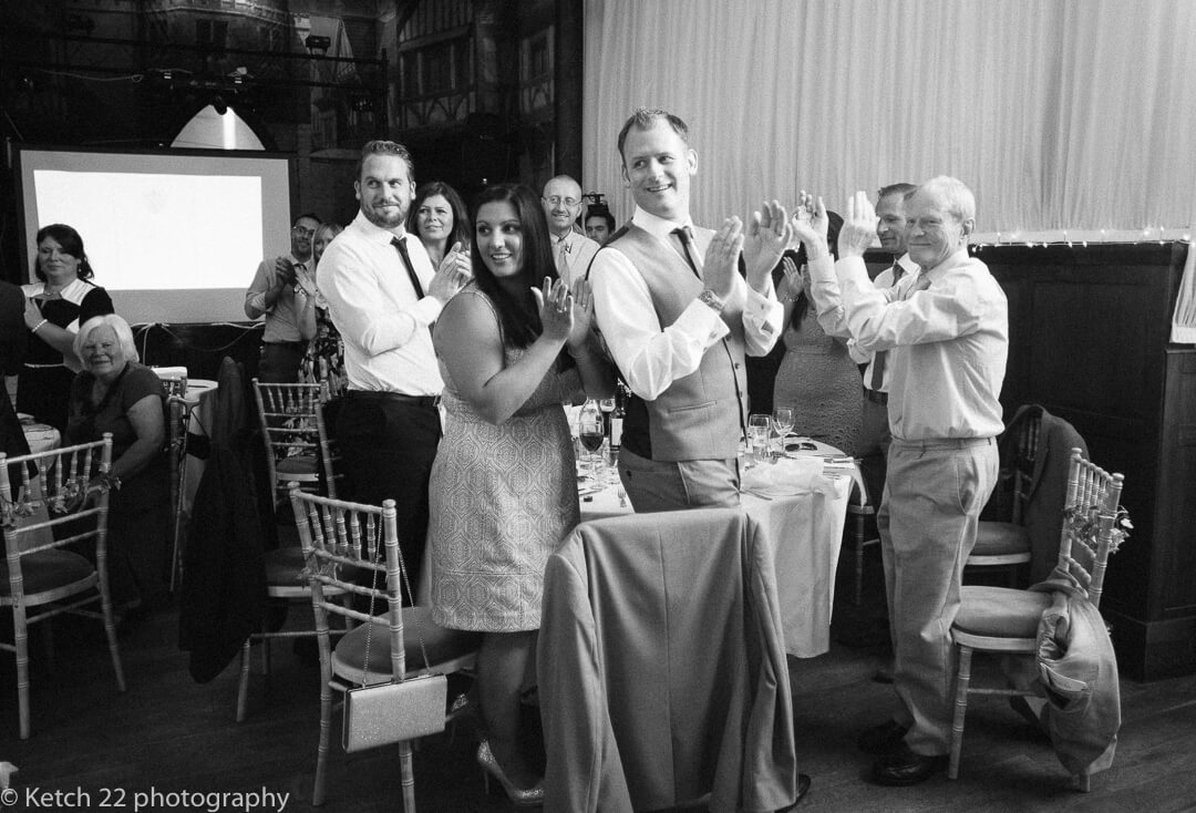 Wedding guests cheer as bride and groom enter dinning room