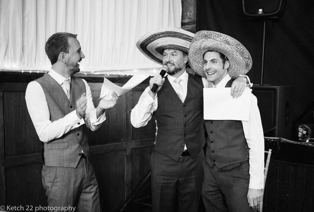 Groom and best man wearing mexican hat at wedding speeches