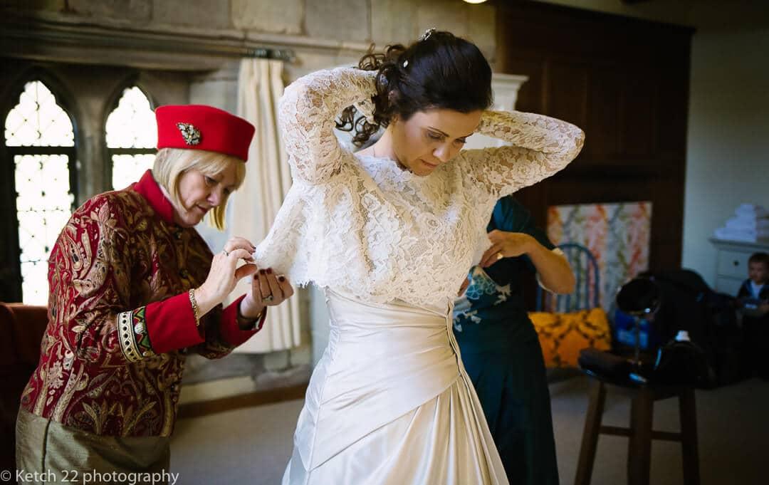 Bride putting on wedding dress at Brinsop Court