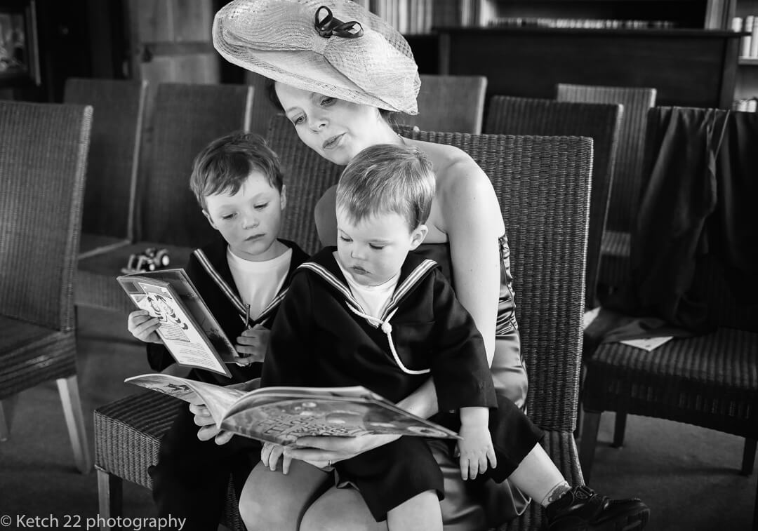 Mother with two small boys sat on her lap reading at Herefordshire wedding