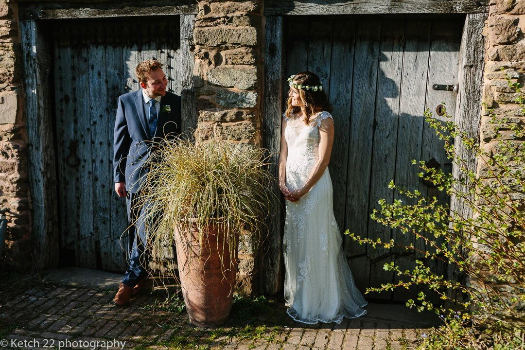 Portrait of bride and groom in front of rustic blue doors