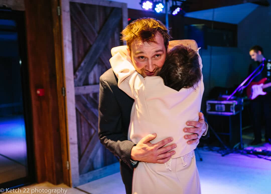 Groom getting hug from grandma at wedding reception