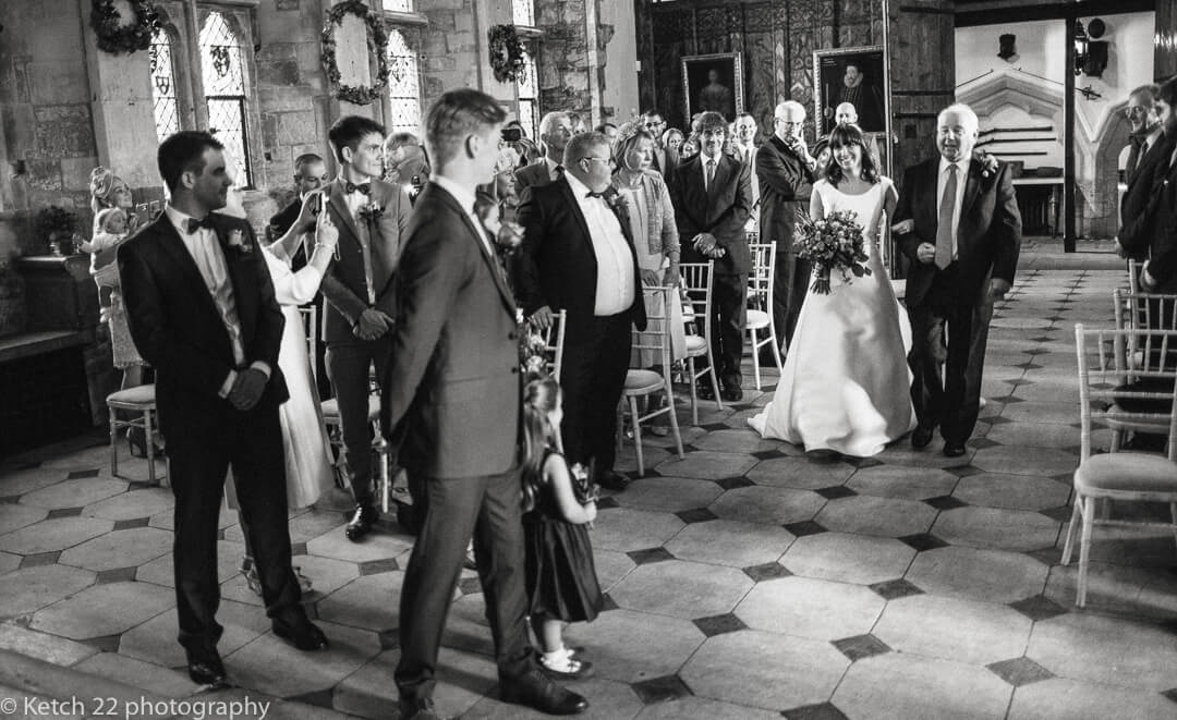 Groom looking at bride as she enters wedding ceremony room at Berkeley Castle