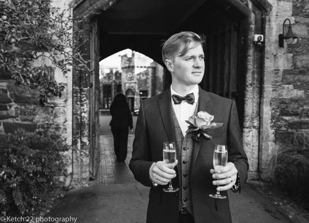 Groom takes a quiet moment with drink at Winter Wedding