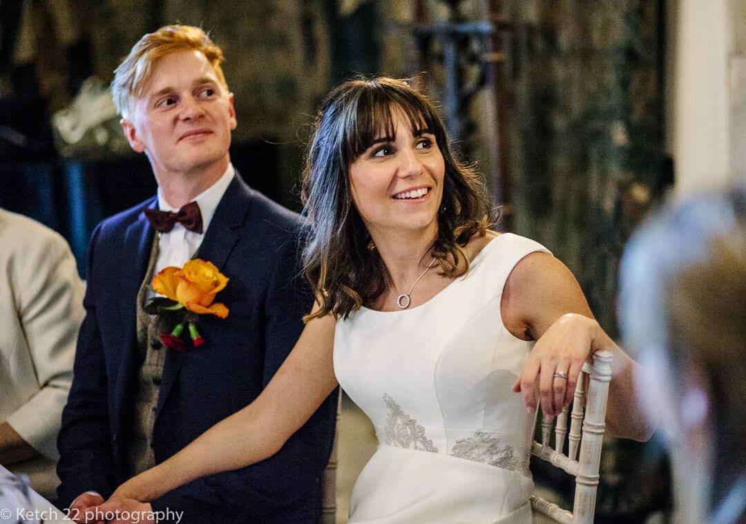 Bride and groom listening to wedding speech