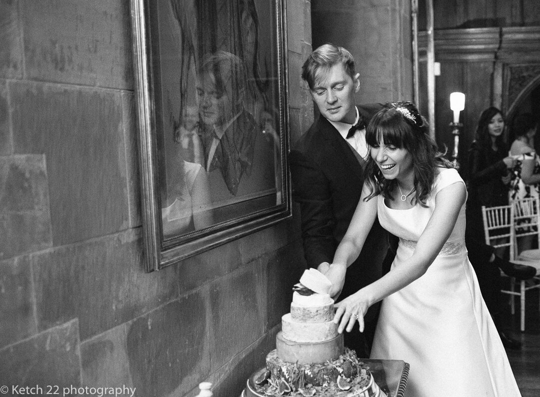 Funny quirky photo of bride and groom cutting wedding cake