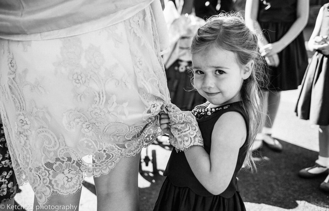Shy flower girl clinging on to Mums dress at wedding