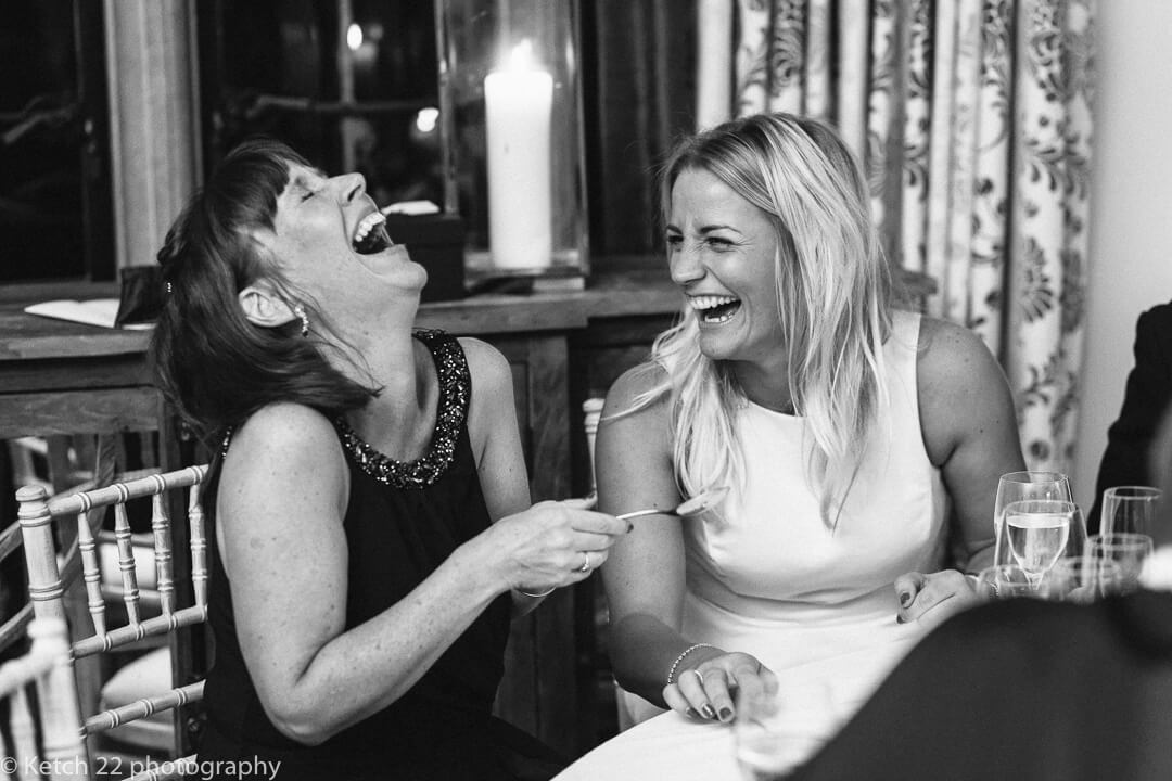 Wedding reportage photo of two women laughing