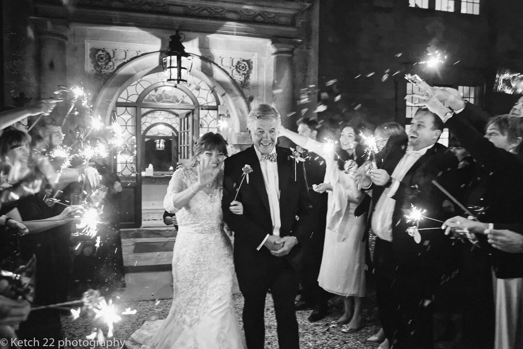 Candid photo of bride and groom walking through a tunnel of sparklers at winter wedding