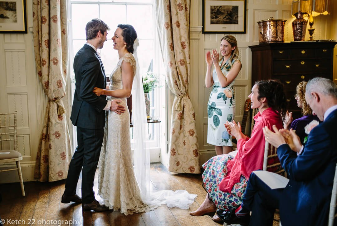 Wedding guests cheering after bride and groom complete vows at wedding ceremony