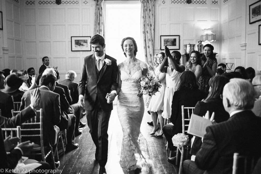 Happy bride and groom leaving wedding ceremony room at Homme House