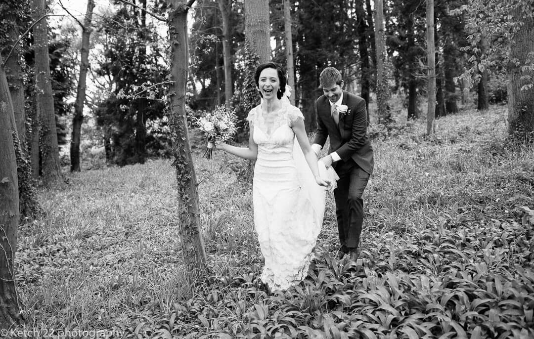 Groom carrying brides dress as she is laughing