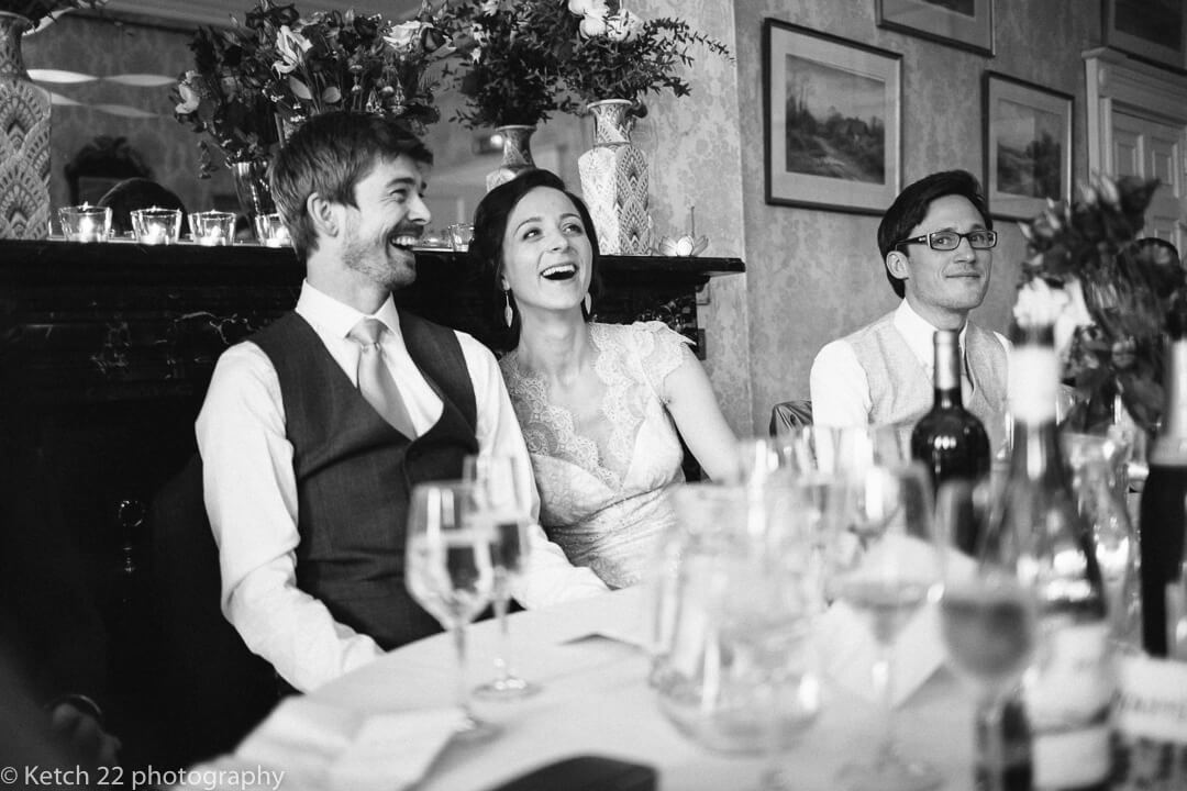 Bride and groom laughing at wedding speeches in Herefordshire