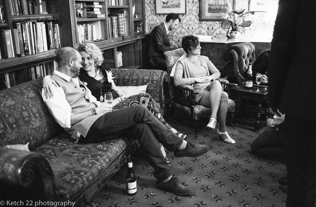 Natural wedding photo of guests relaxing in lounge at country House