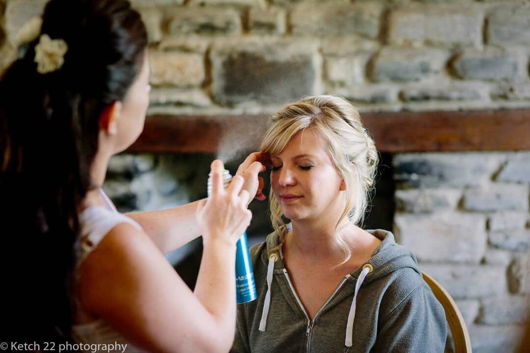 Bride having her hair done at wedding preparations at The great Tythe Barn