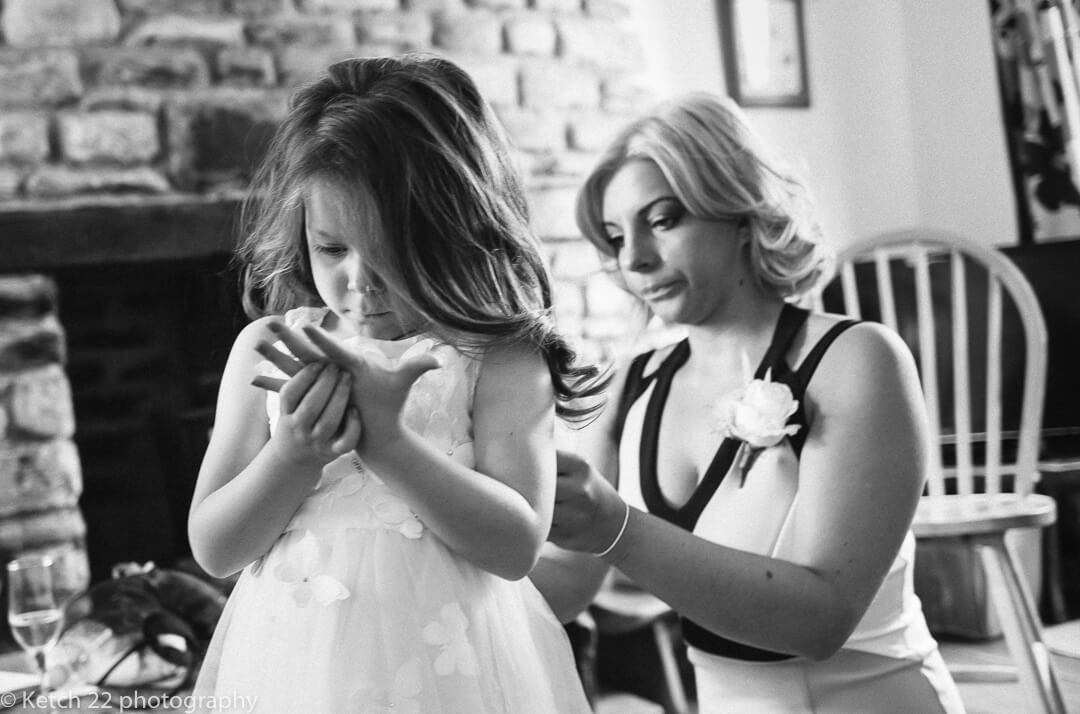 Bridesmaid helping page girl get ready at wedding prepartions