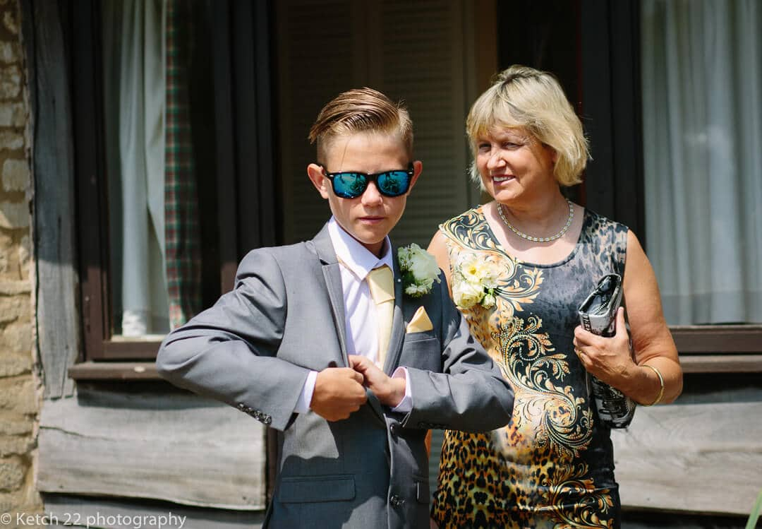 Page boy wearing blue sunglasses at wedding with mother