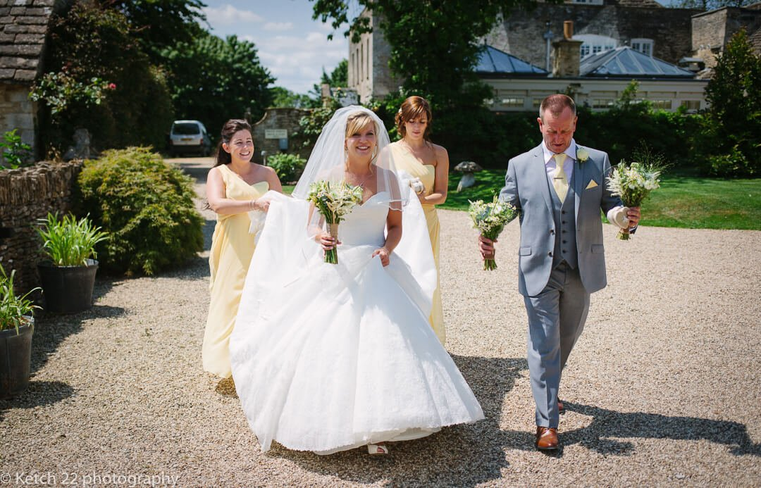 Bride and bridesmaids walking towards Great Tythe Barn for wedding ceremony