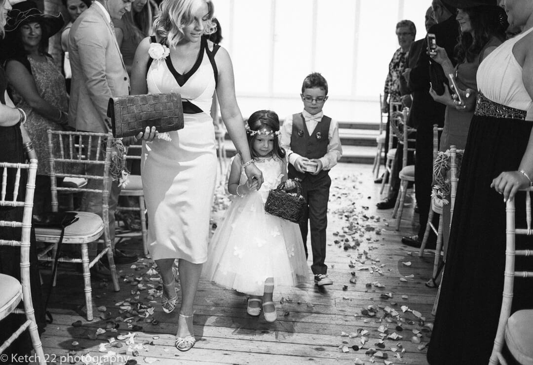 Page girl and page boy walking down aisle at Barn wedding ceremony