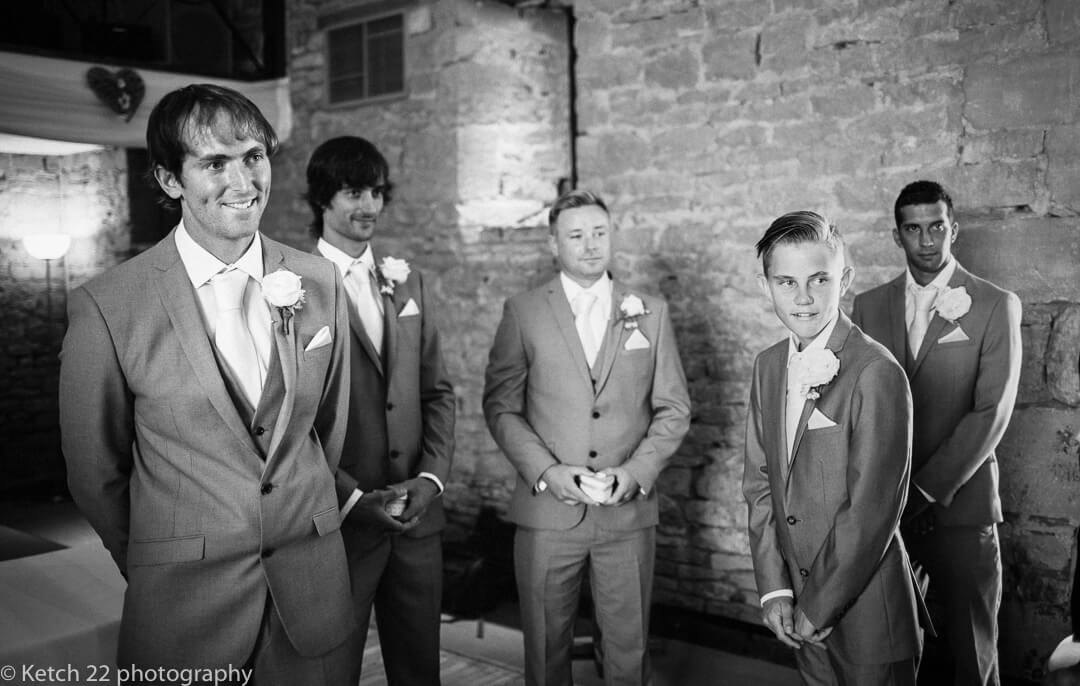 Groom and ushers looking at bride as you enters the wedding ceremony in Gloucestershire