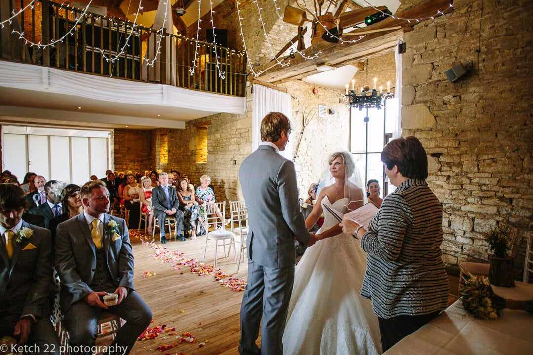 Bride and groom looking ta eachother during wedding ceremony at Great Tythe Barn in Tetbury